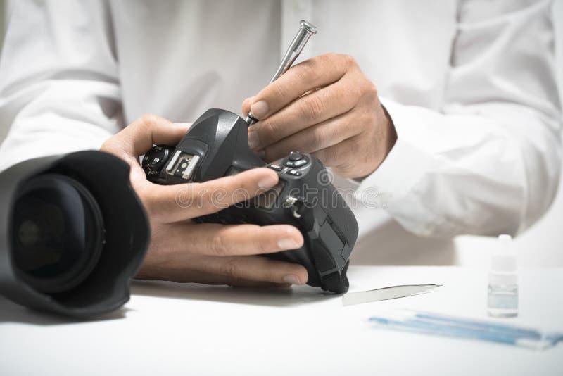 Limpieza, reparación o mantenimiento de la cámara digital fotos de archivo