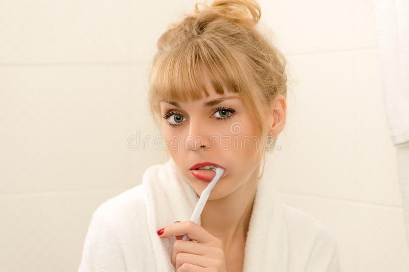 Limpieza rubia atractiva de los dientes de la mujer imagen de archivo
