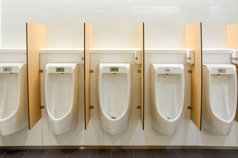 Limpios baños públicos modernos, fila de urinarios de cerámica blanca con lavado automático de sensores y partición de madera imagen de archivo