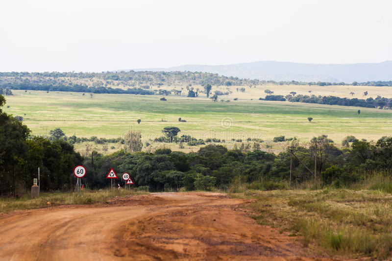 Limpopo farm road. A farm dirt road in the rural province of Limpopo, South Africa with road speed signs on the side of the road. A large field sits waiting to stock photo