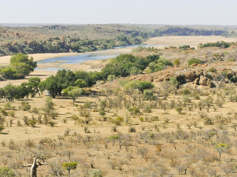 Limpopo river crossing the desert landscape of Mapungubwe Nation. Al Park, travel destination in South Africa. Braided Acacia and huge Baobab trees with red royalty free stock images