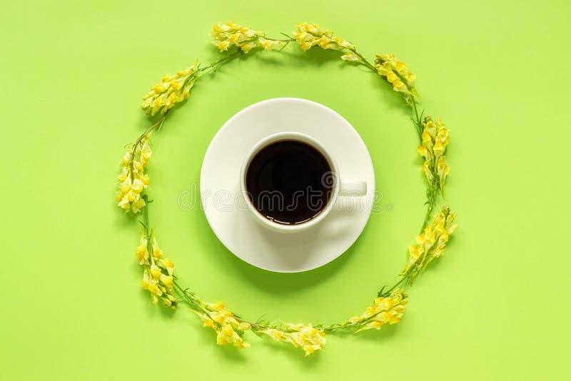 Linaria amarelo das flores selvagens do quadro da xícara de café e da circular no bom dia colocado plano de papel verde do concei foto de stock royalty free