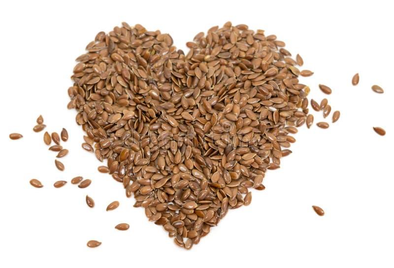 Linaza cruda de las semillas de lino de la foto de la dieta de la comida sana común de la atención sanitaria en forma de corazón foto de archivo libre de regalías