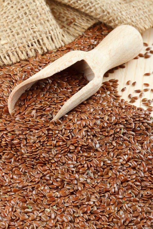 Linaza, semillas de lino, cucharada de madera, saco fotografía de archivo libre de regalías