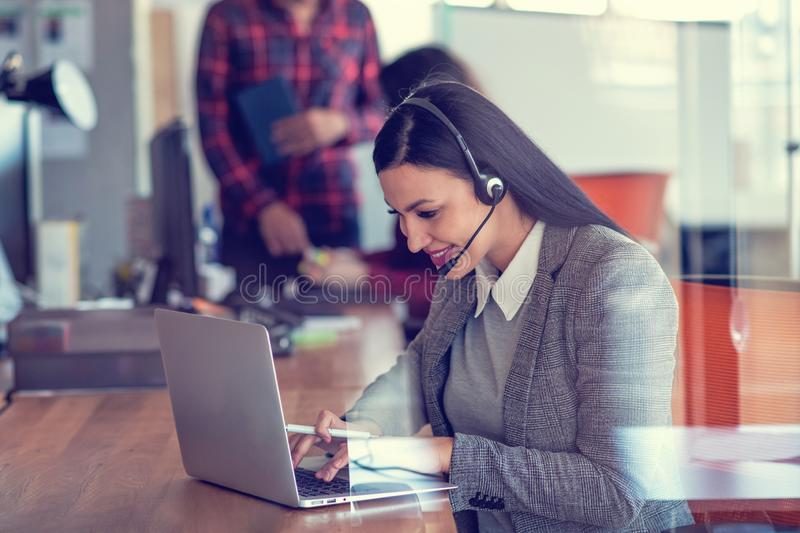 Linda agente de call center navegando pela internet em seu computador imagens de stock