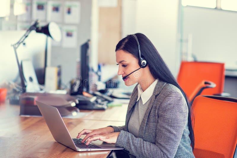 Linda agente de call center navegando pela internet em seu computador fotos de stock