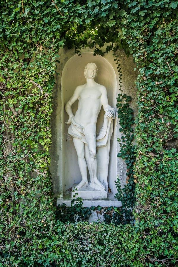 Linda cobertura do parque com a antiga estátua romana branca do homem Tópico Verde Lush imagem de stock royalty free