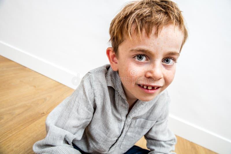 Linda criança com sardas e um sorriso de dente perdido sentada fotos de stock