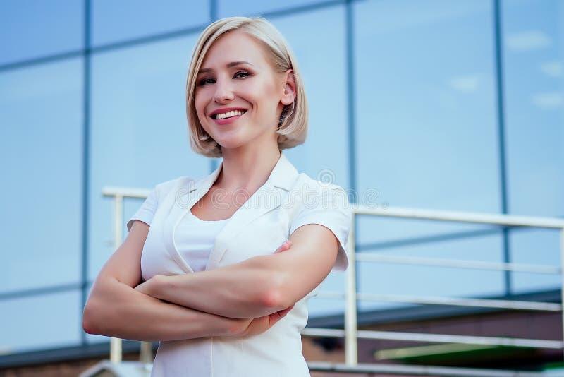 Linda e atraente corte de cabelo curto e loiro, bem-sucedida e independente mulher empresária em um casaco branco posando fotografia de stock