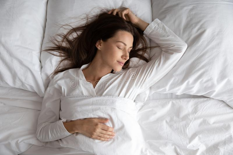 Linda e pacífica senhora relaxante dormindo num leito confortável, vista de cima fotografia de stock