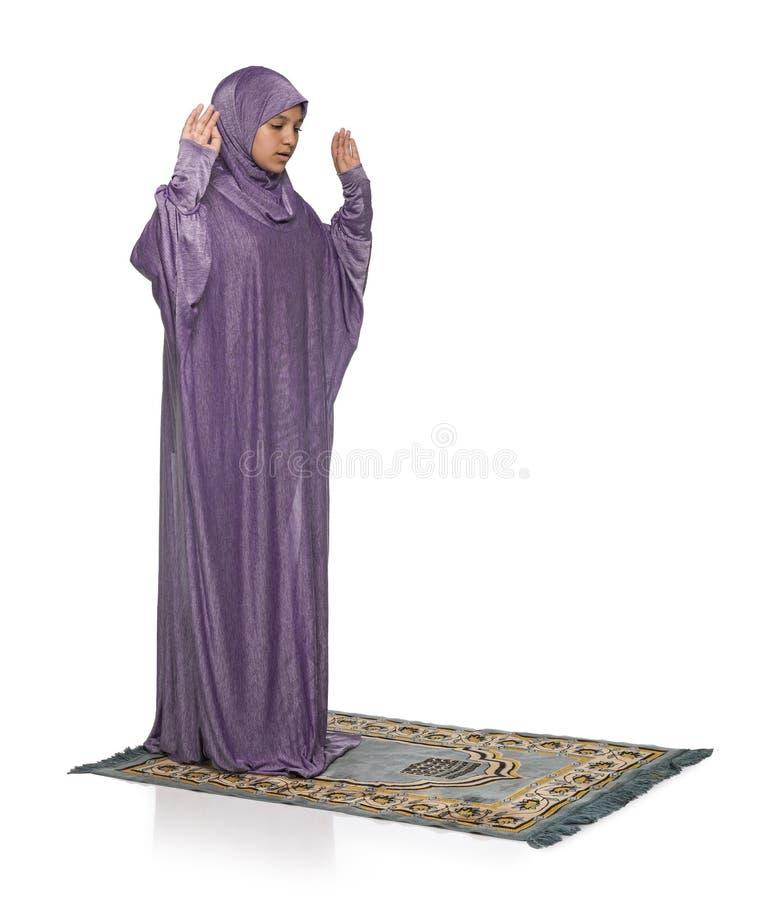 Linda garota árabe rezando usando roupas muçulmanas, armas levantadas foto de stock royalty free