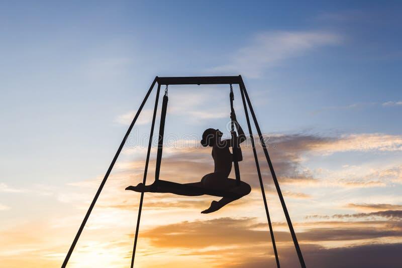 Linda garota praticando poses de ioga-mosca em uma rede ao ar livre foto de stock