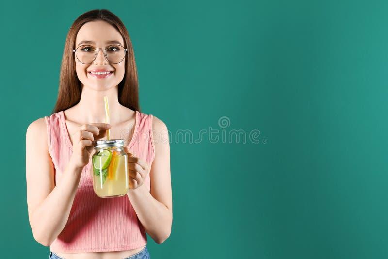 Linda jovem com Mason jar de limonada de detox em fundo verde. Espaço para texto imagem de stock royalty free