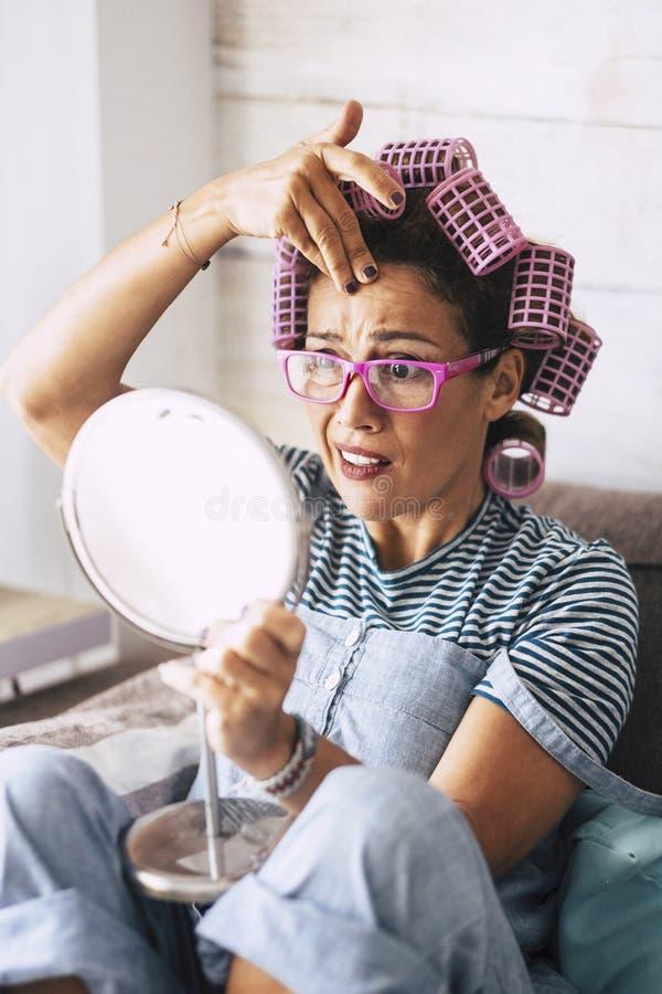 Linda jovem de meia-idade, mulher caucasiana verifica rugas em casa com o morrir durante a preparação da atividade - os curlers d fotografia de stock