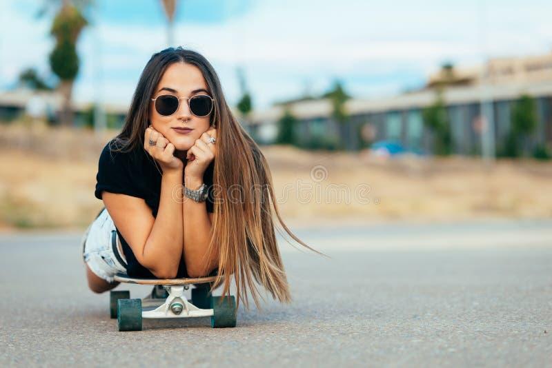 Linda jovem deitada no skate foto de stock
