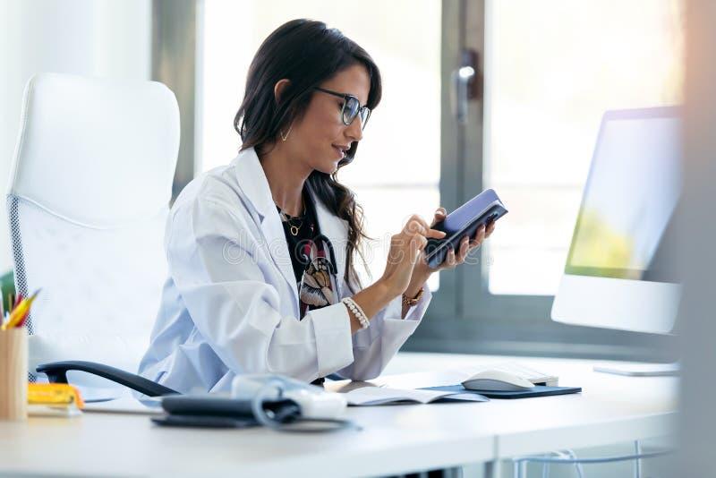 Linda jovem ginecologista usando seu celular antes de iniciar a consulta na clínica imagens de stock