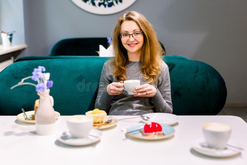 Linda jovem sentada e tomando café ou chá Fechamento de uma jovem loira sentada à mesa com fotos de stock