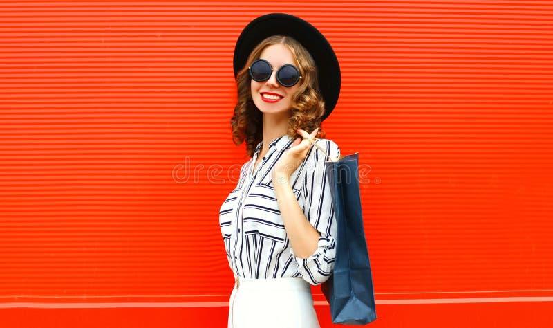 Linda jovem sorridente com sacos de compras usando camisa branca listrada, chapéu preto redondo na rua da cidade sobre a parede v foto de stock