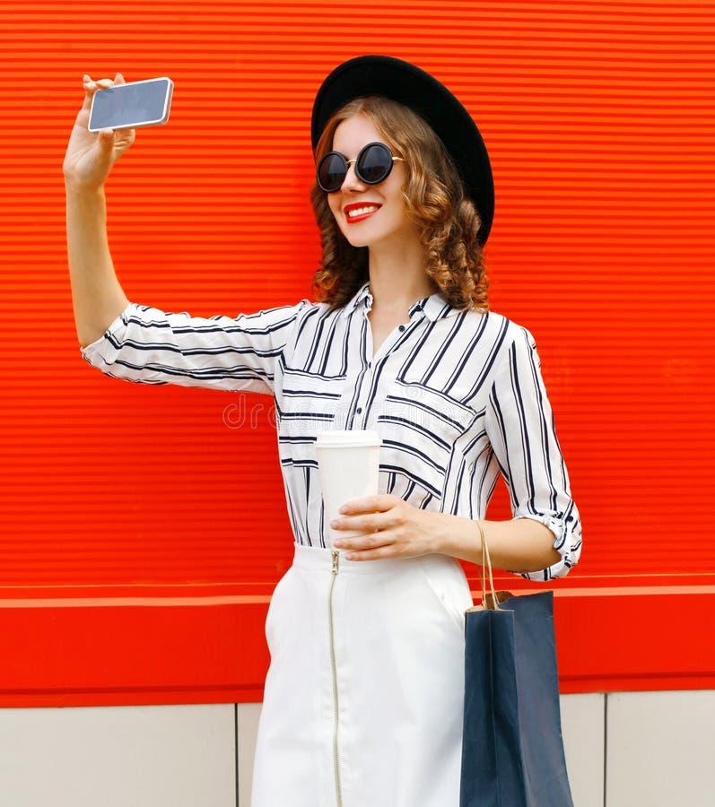 Linda jovem sorridente tirando fotos selfiadas por smartphone com café e sacos de compras usando camisa listrada branca, foto de stock