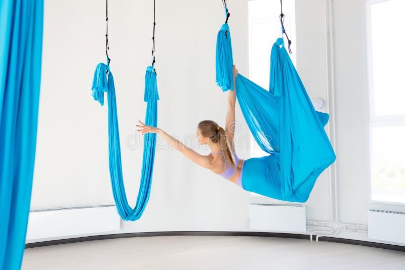 Linda jovem sorrindo para praticar ioga aero-mosca em um estúdio branco em martelos azuis Conceito alongamento imagens de stock