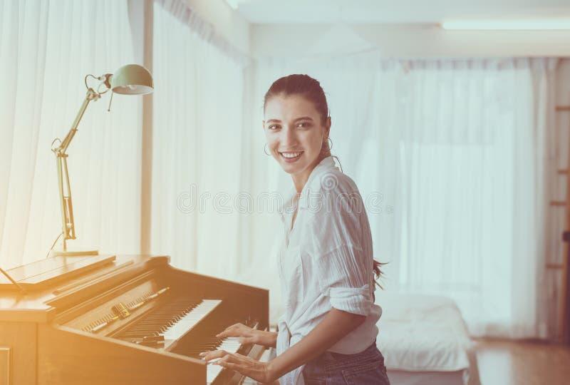 Linda jovem tocando piano, feliz e sorridente, tempo de relaxamento imagens de stock royalty free