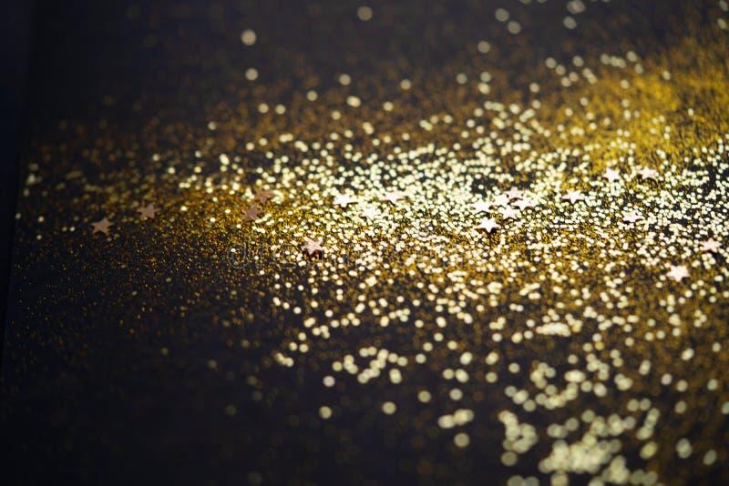 Linda luz de Natal Glitter abstrato e faíscas dispersas em cor dourada, a preto imagem de stock