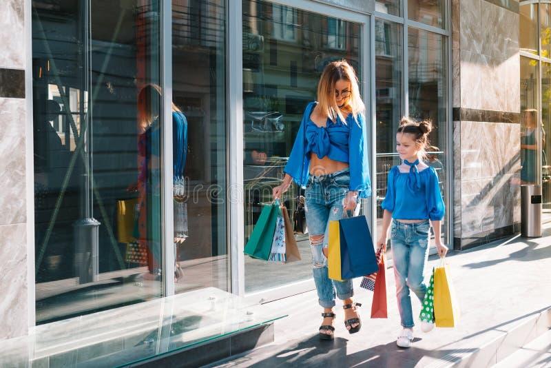 Linda mãe e sua filha bonitinha estão segurando sacos de compras, olhando para a câmera e sorrindo ao ar livre imagem de stock