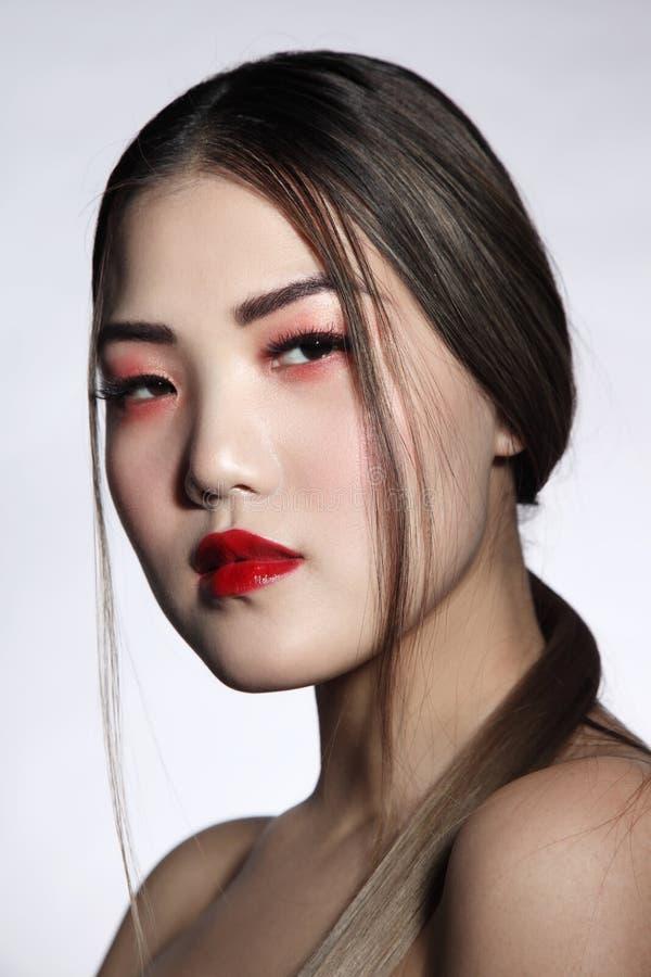 Linda menina asiática com cabelo comprido e batom vermelho imagem de stock