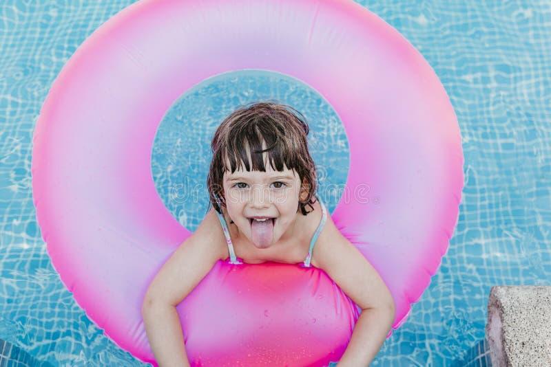 linda menina flutuando em donuts cor-de-rosa numa piscina Sorrir Diversão e estilo de vida de verão foto de stock