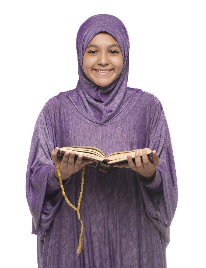 Linda moça árabe muçulmana em moda islâmica se veste segurando o Santo Livro do Corão com uma cara sorridente e feliz foto de stock