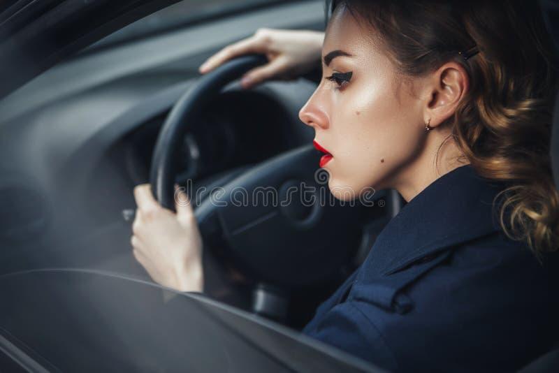 Linda morena sexy agente de espiões assassino ou policial na jaqueta de couro e jeans com uma arma na mão dirigindo um carro depo fotos de stock
