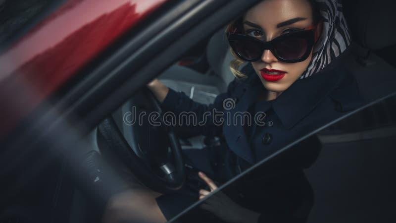 Linda morena sexy agente de espiões assassino ou policial na jaqueta de couro e jeans com uma arma na mão dirigindo um carro depo fotografia de stock royalty free