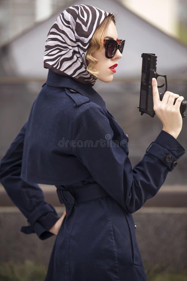Linda morena sexy agente espião assassino ou policial na jaqueta e óculos de sol com uma arma na mão, para foto de stock royalty free