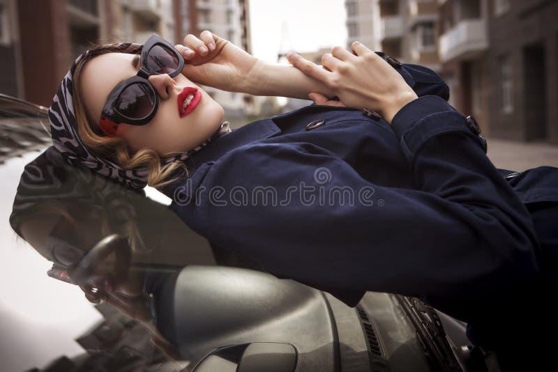 Linda morena sexy agente espião assassino ou policial na jaqueta e óculos de sol com uma arma na mão, para foto de stock