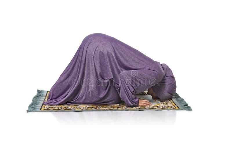 Linda mulher árabe rezando usando roupas muçulmanas, ajoelhando-se imagens de stock