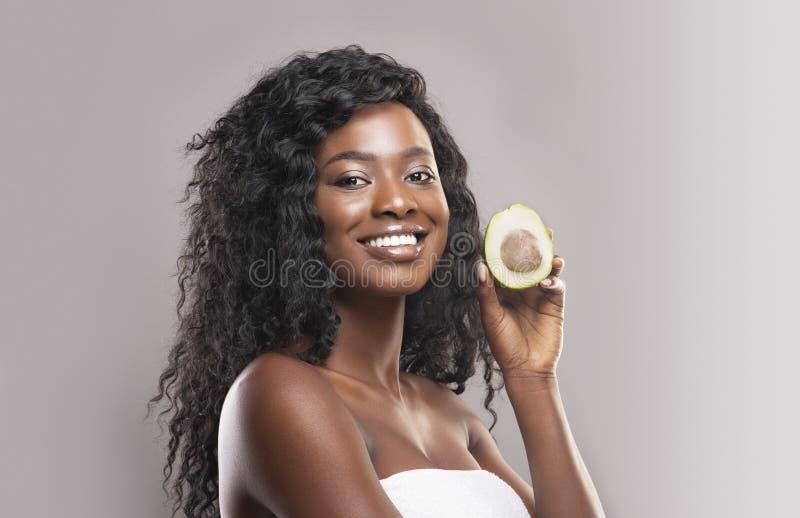 Linda mulher africana que segura meio abacate fotografia de stock