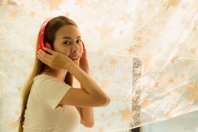 Linda mulher asiática descansando, ouvindo música com fones de ouvido vermelhos, com livros e tablet, na cama feliz em casa com r imagens de stock