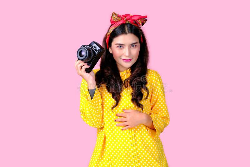Linda mulher com headband vermelha e vestido amarelo seguram a câmera preta em frente ao fundo rosa, também com conceito de retrô imagens de stock royalty free