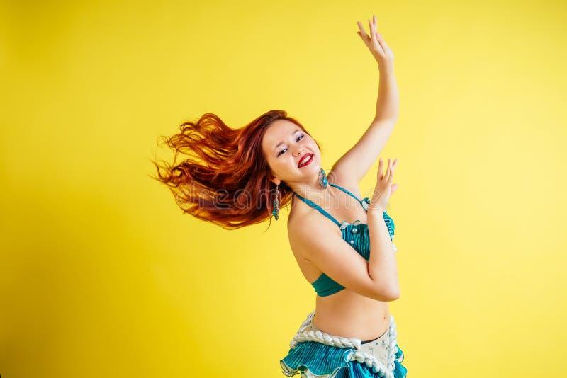 Linda mulher de cabelos vermelhos dançando barriga oriental dançando de terno azul em fundo amarelo em estúdio foto de stock