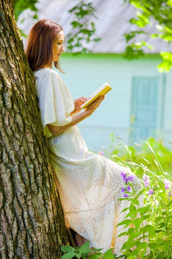 A linda mulher de vestido branco lê um livro fotografia de stock