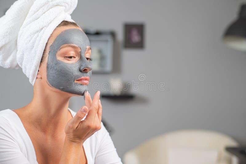 A linda mulher está aplicando máscara de barro facial. Tratamentos da beleza e do céu foto de stock royalty free