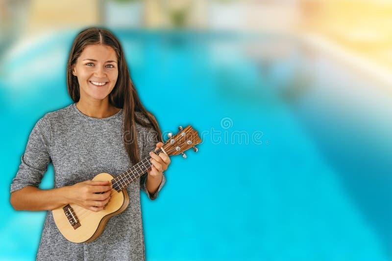 Linda mulher feliz tocando violão ukulele em um fundo desfocado de piscina imagens de stock royalty free