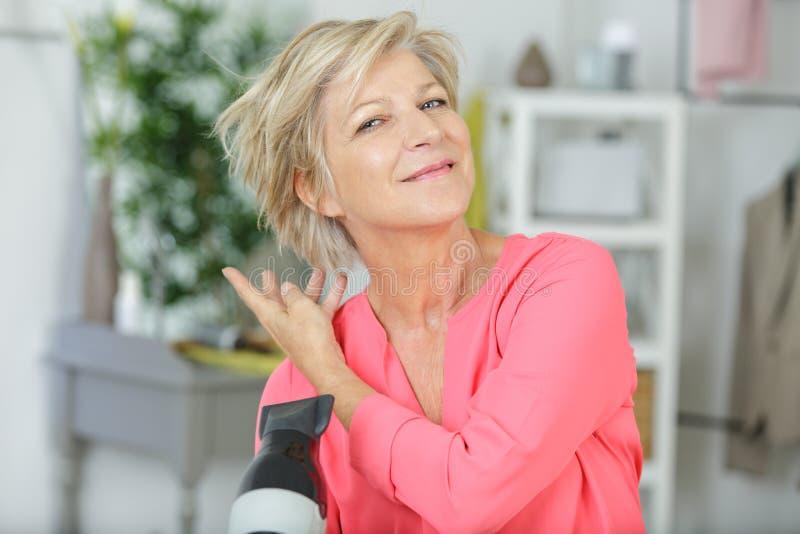 Linda mulher idosa secando cabelo imagens de stock royalty free