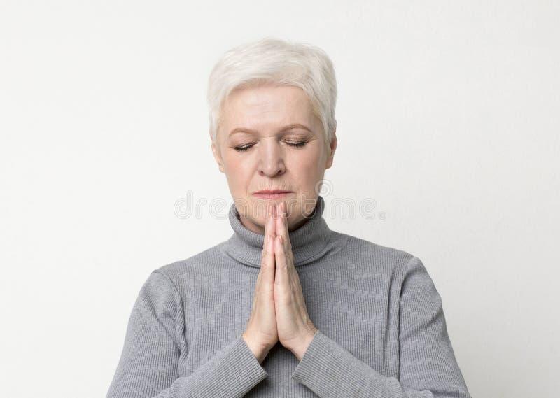 Linda mulher madura rezando com as mãos apertadas na cara imagens de stock