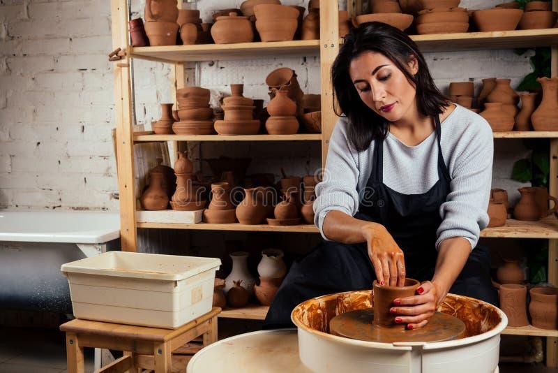 Linda mulher mestre em cerâmica moldes de vaso de argila em Márstre mulher escultora trabalha com argila no volante de Potter foto de stock royalty free