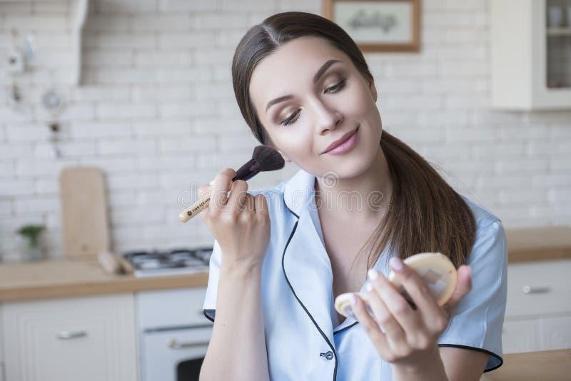Linda mulher morena em casa no pijama Ela faz procedimentos de beleza - aplica blusher com um pincel Luz natural Estilo de vida imagens de stock