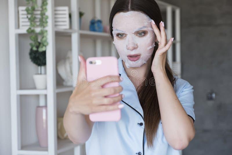 Linda mulher morena em casa no pijama Ela faz procedimentos de beleza - aplica máscara humilhante e faz selfie nela fotografia de stock