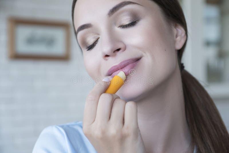 Linda mulher morena em casa no pijama Ela faz procedimentos de beleza - pinta os lábios usando batom Luz natural Estilo de vida fotos de stock