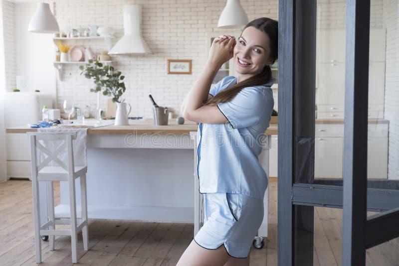 Linda mulher morena em casa no pijama Ela toma café da manhã na cozinha Luz natural Conceito de cuidados de saúde estilo de vida imagens de stock royalty free