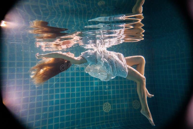 Linda mulher posando debaixo d'água de vestido branco imagem de stock
